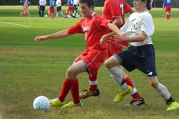 Tewksbury's Benn LaFortune (9) holds off a Dracut defender.