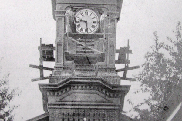 The steeple of the Presbyterian church, at 44 W. Main St., with workmen perched on scaffolding surrounding the clock.