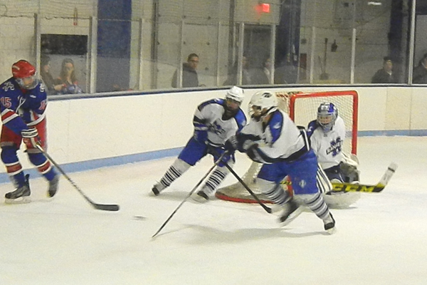 Senior forward Steve Hamel (15) passes the puck to the front of the net.