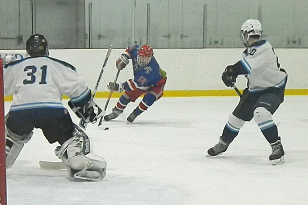 Senior forward David Dempsey (12) turns the corner and attacks the Wilmington net.