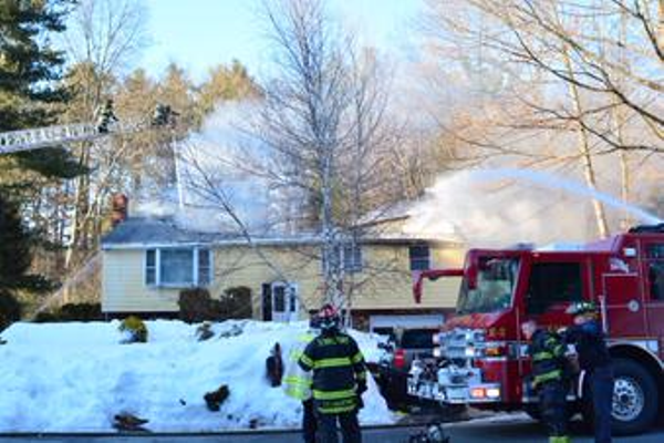 Photo by Rich MacDonald. Tewksbury Firefighters battle a blaze at 85 Rounsevell Ave. on Monday.