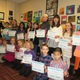 Students from the Unionville-Chadds Ford School District were recognized by the school board and administration on March 9 for contributing their artworks to the lobby area of the District Office Art Beat instructor Samantha Hage is at left