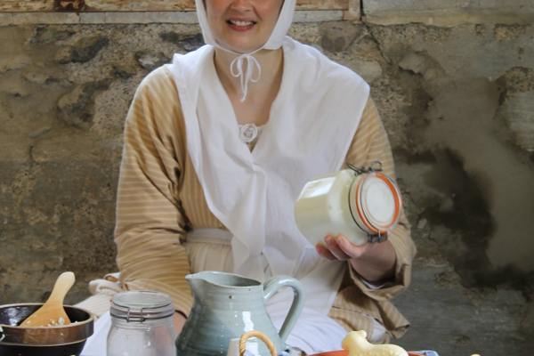 Visitors are welcome to shake cream in a jar to help make butter, just as Rebecca Anderson, Watsontown, demonstrates.  Rebecca will describe what is needed to make butter, as was done on local farms throughout our history.  Her display includes butter molds and wooden butter-making tools, homemade molded butter and plain and flavored samples for tasting.   Photo by Pat Longley.