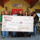 Fuzzy's Taco Shop Founder/President Chuck Bush (center) and others hold $20,000 from October 2014 charity golf fundraiser.