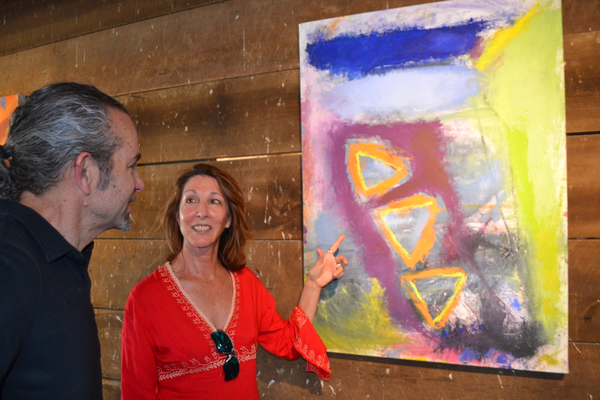 Wilmington-based abstract artist Mia Muratori discusses one of her canvases with Wilmington sculptor Dennis Beach.
