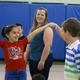(L-R): Second grader Aris Pavel and Braedon Murphy (striped shirt) dance while teacher Nikole Auger waits her turn
