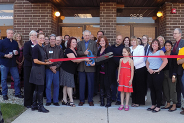 Mayor Joe Broda, Village of Lisle, cuts the ribbon for the grand re-opening of WFH Enterprises, Inc. and PEO Solutions, with Liz O'Toole, WFH Enterprises, Inc. and Candace Coyne, PEO Solutions. Kindercare, Eisenhower
