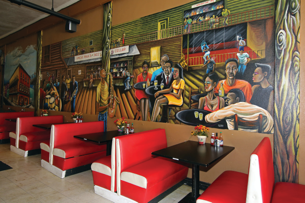 Navarro, a local homeless artist, created the mural that runs along the length of the wall in the café. It is a work in progress, with the saxophonist being the most recent addition.