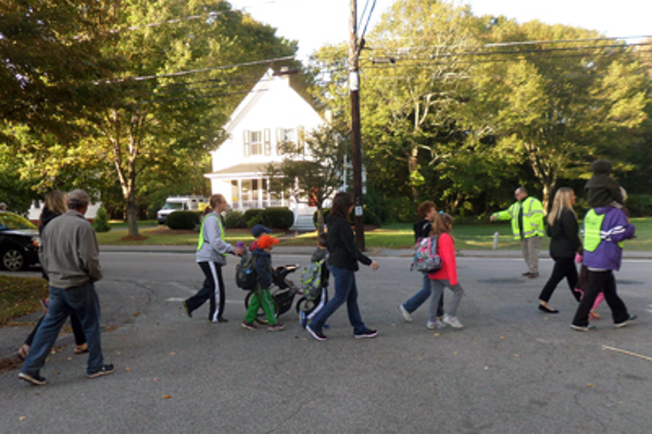 Officer Len Gosselin directs group walking in the Safe Routes to school event across Ray avenue on their way up Maple Street to Stall Brook School