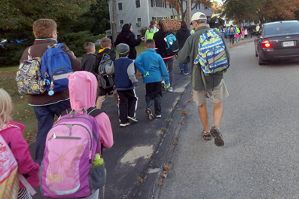 Children, parents, teachers, and Stall Brook Principal Carolyn Rafferty, head down Plymouth Road in Bellingham, accompanied by a Bellingham police escort, including Officers Len Gosselin and Doug Houston and Lt. James Russell