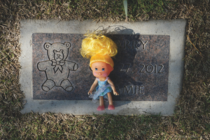 A tiny doll left by an unknown mourner rests on a headstone at the Garden of Innocence in Mountain View Cemetery in Fresno