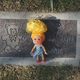 A tiny doll left by an unknown mourner rests on a headstone at the Garden of Innocence in Mountain View Cemetery in Fresno.