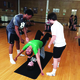 After receiving instruction and a video example from teacher Vanessa Snopek, students practice the 'Flyer' pose. This is a three-person pose: one person is the base, one is the spotter, and one is the flyer.