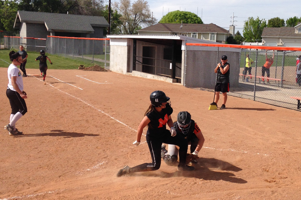 One of the Spartan's Varsity players collides with the pitcher as she slides into home base. Head coach Lisa Parker, who has coached at Murray for 25 years, encouraged the girls to be more aggressive defensively this season.