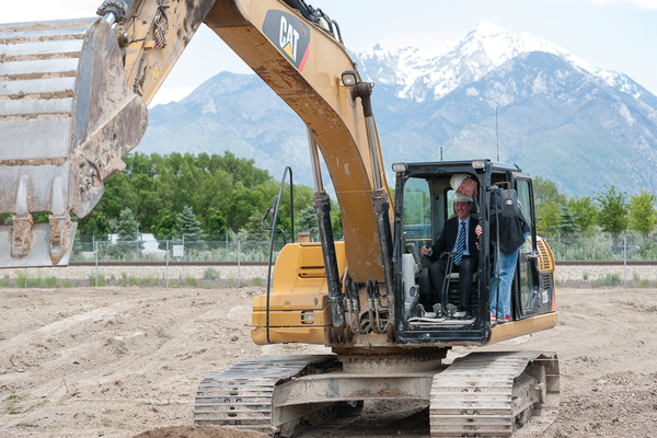 Salt Lake County Mayor Ben McAdams and John Sperry, CEO of InMoment, use an excavator to break ground at SoJo Station where InMoment and other tech companies will have immediate access to public transportation. – InMoment
