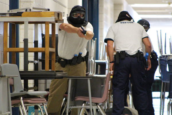 "A Peace Officer and Standards Training cadet acts as cover for members of his squad detaining Utah Highway Patrol Trooper Daniel Krum who acted as an ""active shooter"" at Jordan High School on July 5, 2016. (Photo: Chris Larson, Sandy City Journal)"