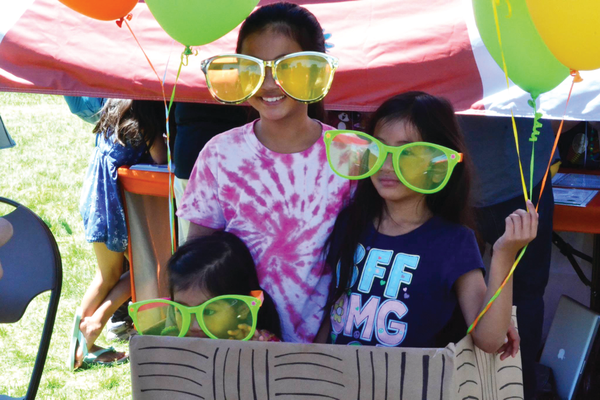 Girls pose for a picture with giant sunglasses at Salt Lake County Library Service's summer reading challenge kick-off event. – Salt Lake County Library Services
