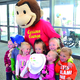 A curious George mascot poses for pictures with children at Salt Lake County Library Service's summer reading challenge kick-off event. – Salt Lake County Library Services