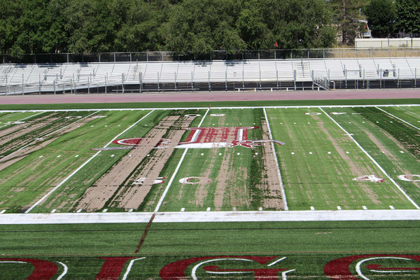 Sand laying on top of the artificial turf overlay at midfield of the Jordan High School turf field before the spreader lifts the turf up and distributes the turf's fill. (Photo: Chris Larson, Sandy City Journal)