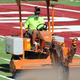 """Kyle Falslev, FieldTurf superintendent and installer, runs the """"spreader"""" over the south portion of the Jordan High School turn field, throwing up cryogenically frozen then crushed rubber crumbs which act as fill for the turf. (Photo: Chris Larson, Sandy City Journal)"""