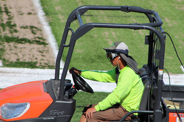 FieldTurf employee Cole drives to the north side of the Jordan High School turf fielded to dump the base layer of sand for the turf's fill. (Photo: Chris Larson, Sandy City Journal)
