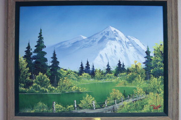 The untitled painting by Bob Ross, which hangs at Draper Elementary, was given to the Draper Arts Foundation by member Jean Hendericksen. Her brother studied under Ross. — Julie Slama