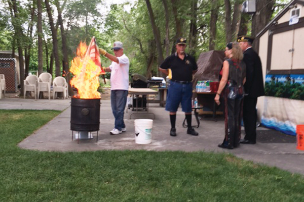 Flags were dipped in fuel before being placed in a fire canister. Over 70 people attended the flag retirement ceremony held at the American Legion Post 112 in Murray on Flag Day, June 14. —Susie Brass
