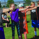 Children practice archery techniques using a string bow. – Tori La Rue