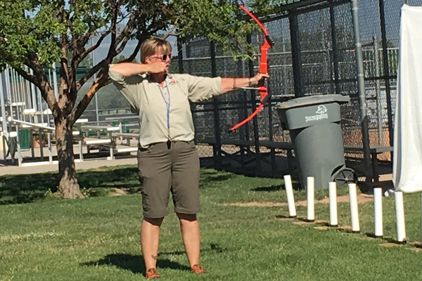 RaLynne Takeda, a representative from the Divison of Wildlife Resources, demonstrates the form an archer should have when prepping to shoot. Along with teaching archery courses in South Jordan during the summer, Takeda helped bring archery to 95 PE classes across the state. – Tori La Rue