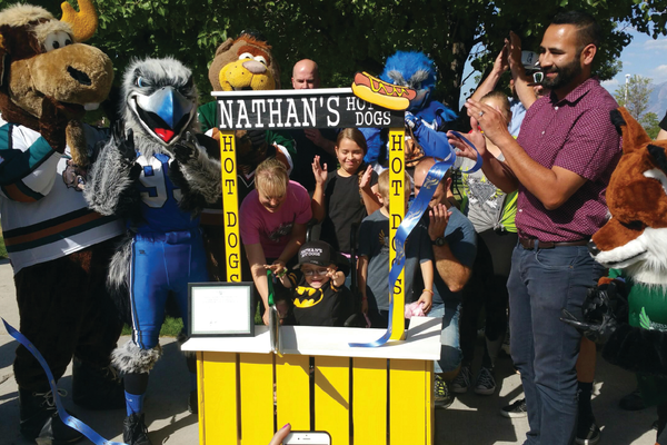 Nathan Glad cuts the ceremonial ribbon at the grand opening of his hot dog stand. Mascot Miracles, an Eagle Scout and community members worked together to bring about the event. –Melissa Worthen