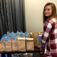 Ryilee Stratton, 12, stands by the table of gift packages her family put together for the West Jordan Police Department. –Tori La Rue