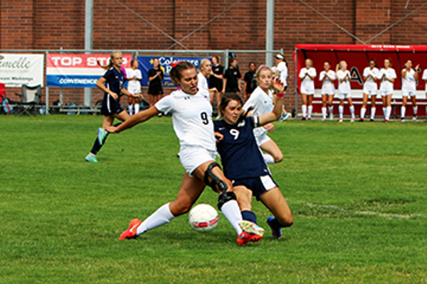 Senior striker Sadie Mertlich fights off a defender. (Michelle Porter/Resident)