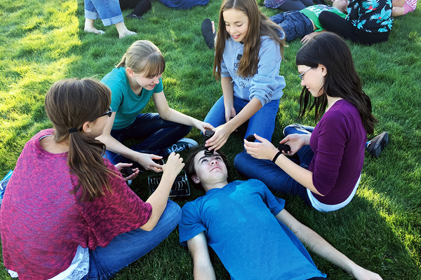 Teens stacked Oreos on each other's foreheads during one of the last rounds of the Bingham Creek Library Chocolate Olympics. (Tori La Rue/City Journals)