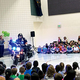 Officer Andrew Hercules of the West Jordan Police Department drives a motorcycle inside the Heartland Elementary School gym surrounded by the student body. (Tori La Rue/City Journals)