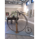 A penny farthing bicycle stands in the center of the gallery.