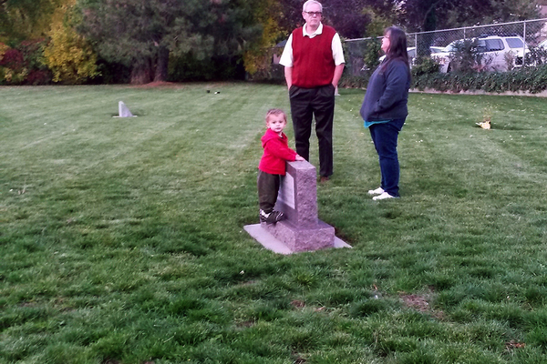 Councilman Tee Tyler discussing his new knowledge of history with Ann Bracken while her son Joseph plays around the tombstones. (Cassie Goff/City Journals)