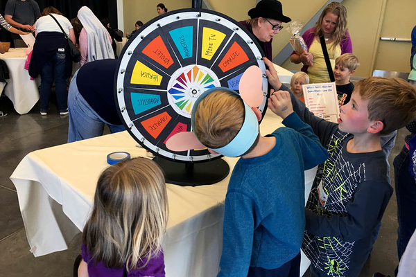 "Children spin a wheel to determine which character from ""Charlie and the Chocolate Factory"" they are at the Viridian Event Center's Roald Dahl Day celebration on Oct. 7. (Tori La Rue/City Journals)"