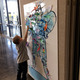 """Isaac Powell, 4, hangs a paper newt he colored on the paper cut-out of """"The Trunchbull,"""" a character from the children's book """"Matilda."""" Isaac and other community children celebrated Roald Dahl's books at the Viridian Event Center on Oct. 7. (Tori La Rue/City Journals)"""