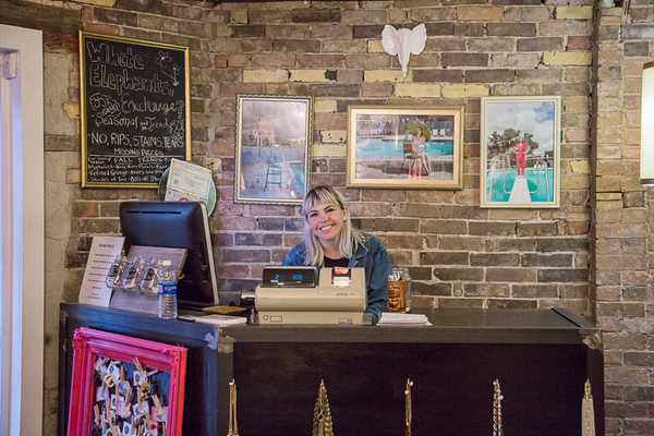 The interior of The White Elephant Exchange with Rachael LePrey, owner of the store, at the front counter.