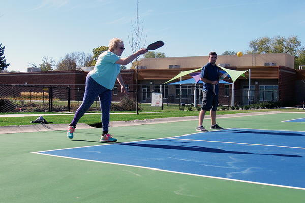 Connie Andersen serves the Whiffle Ball with teammate Dustin Permann to christen the new pickleball courts on Oct. 27 at the Columbus Center. (Travis Barton/City Journals)