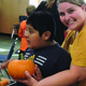 A para-educator hands a Hartvigsen School student a pumpkin. The pumkins were donated by the Salt Lake County Sheriff's Office and were grown through the county jail's horticulture program. (Taylorsville City)