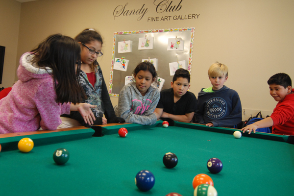 : Jordan McDaniel, Hervie Cortez, Kelsy Alfaro, Mycaella Prada, Julianna Perez, Miguel Cortez and Fisher Jarvis enjoy a game of pool. (Keyra Kristoffersen/City Journals)