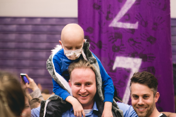 Darren Hall, 6, sits on his dad's shoulders after Riverton High School student government officers announced the grand total students raised in their charity drive. Darren was one of the seven children who benefitted from the drive. (Michael Martinez/Riverton High School)