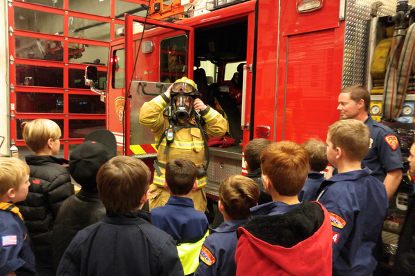 Randy Stevens, UFA paramedic, shows den packs fire-safety gear and respirator. (Patrice Taylor/Den Mom Pack #3384)