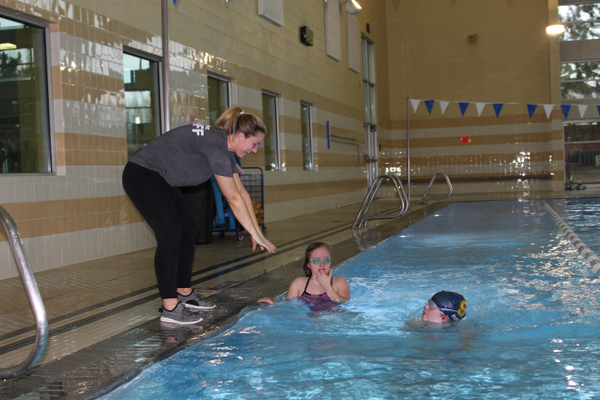 Ivy Hausknecht, adaptive aquatic manager, gives instruction on the swimmers' strokes during a class for the Otter and Adaptive Swim Club. (Travis Barton/City Journals)