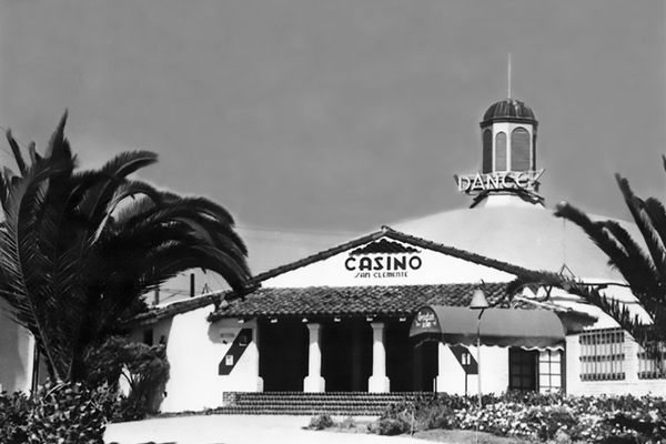 "The Casino San Clemente Community and private center for live music, theater and private events including weddings  GRAND OPENING: July 31, 1937 (Built by the Bank of America at the end of the Great Depression by the Strang Brothers)    Toward the end of the Great Depression, local investors endeavored to attract new home buyers to the struggling ""Spanish Village by the Sea"" development by adding a dance and music hall to welcome visitors alongside the Ole Hanson Beach Club. The iconic red domed ballroom was inspired by the larger Catalina Casino dance hall in Avalon and still boasts incredible acoustics. The Casino San Clemente opened on July 31, 1937 to a rumored 5000 attendees (in contrast to the approximate 500 residents living in San Clemente) with an entrance fee of 40 cents. ""Casino"" is a word drawn from the Italian language meaning ""a gathering place"" and true to intent the Casino San Clemente has a rich history of visiting Hollywood stars including Judy Garland, Mickey Rooney, Cesar Romero, Dorothy Lamour; live national radio broadcasts of big bands on stage; dinner theater evenings and the ocean view Yacht Club restaurant on site... full of vibrant life and dancing visitors arriving via PCH from LA and beyond as well as train along the coast. Over the course of 80 long years, the Casino San Clemente, a nationally reknown big band stage and dance hall, has transitioned as owners, uses and economies have changed. Notable segways have included: a dinner/theater venue featuring many well-known Hollywood legendary stars; Moose Hall; a Coast Guard center during WWII, an Eastern Medicine education center; and now (back to the beginning) a private event and celebration venue. Today, owned by the Sadeghi Family since 2009, after several years of loving restoration the Casino San Clemente is enjoying a renaissance in its 80th anniversary year, thanks to the ongoing love of music and celebration by the local community. It proudly hosts more than 100 private weddings a year, multiple fundraisers and philanthropic endeavors by local business groups, schools and churches; and is enjoying a recent renewal of award winning live music events such as the Spring, Summer and Autumn Jazz Series in the West Wing. Ellie's Table cafe on site now serves the North Beach neighborhood artisan coffees, homebaked pastries and lunch items on its sunny patio. The Sadeghi's look forward to another 80+ years of joyful gatherings and welcoming visitors to the Casino San Clemente. Look for many anniversary events in 2017! b 140 W. Avenida Pico in North Beach, San Clemente (949) 369-6600."