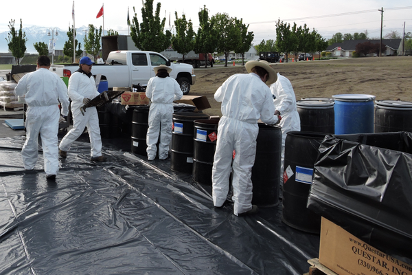 Clad in protective suits, volunteers stow hazardous household waste in barrels. (Taylorsville City)