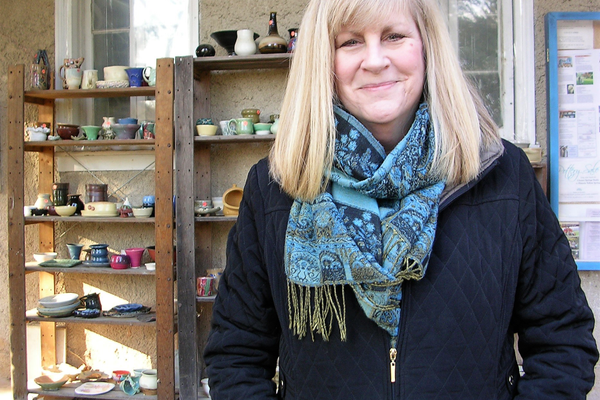 Eileen McMonigle is the executive director at Historic Yellow Springs. Behind her on the shelves are students' ceramic work for sale. (Photo by Natalie Smith)