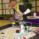 Plan Bee robotics team member puts on an attachment at the state First Lego League robotics tournament where the team won the Teamwork Award. (Julie Slama/City Journals)