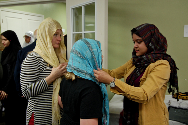 Afrida Nahain helps teach Jenelle and Monae Kingler how to wrap the hijab, a traditional woman's headscarf, around their heads. (Keyra Kristoffersen/City Journals)